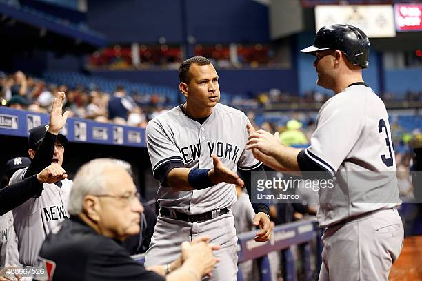 Brian McCann of the New York Yankees celebrates with Alex Rodriguez after scoring off of an RBI single by Chase Headley during the sixth inning of a...