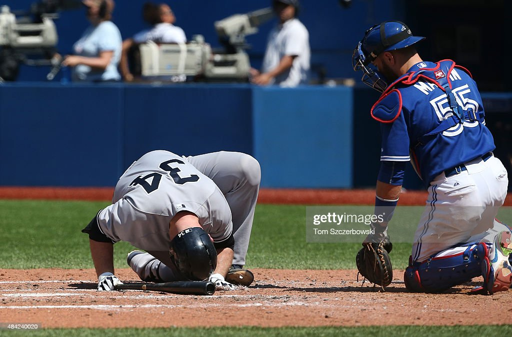 Brian McCann #34 of the New York Yankees falls after being hit by a pitch in the fifth inning during MLB game action as Russell Martin #55 of the Toronto Blue Jays watches on August 16, 2015 at Rogers Centre in Toronto, Ontario, Canada.