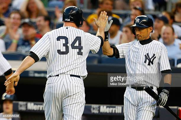 Brian McCann of the New York Yankees is greeted by Ichiro Suzuki after scoring on Martin Prado RBI single in the first inning against the Cleveland...