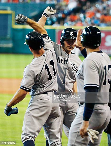 Brian McCann of the New York Yankees is greeted by teammates Brett Gardner and Alex Rodriguez after McCann hit a grand slam in the first inning...