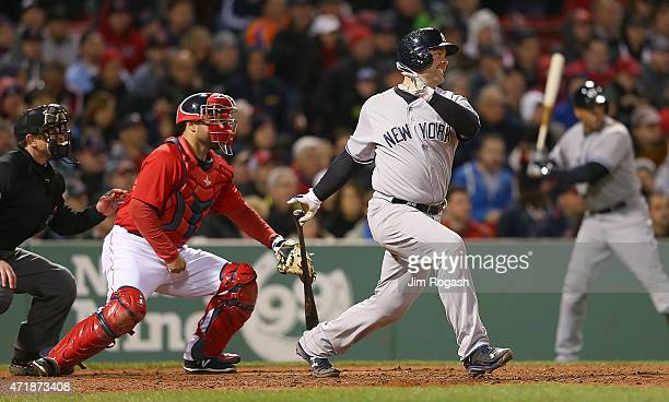 Brian McCann of the New York Yankees knocks in the tying run in the seventh inning as Sandy Leon of the Boston Red Sox defends at Fenway Park May 1...