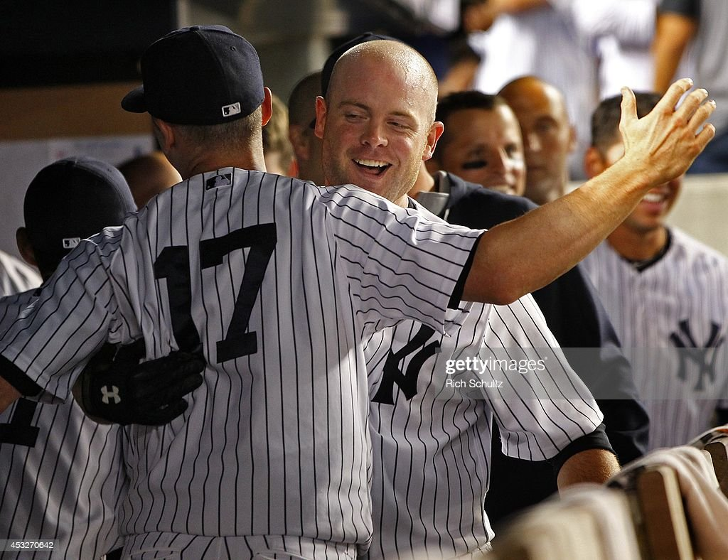Brian McCann #34, right, of the New York Yankees is congratulated by Brendan Ryan #17 after he hit a home run against the Detroit Tigers during the seventh inning of a MLB baseball game at Yankee Stadium on August 6, 2014 in the Bronx borough of New York City.