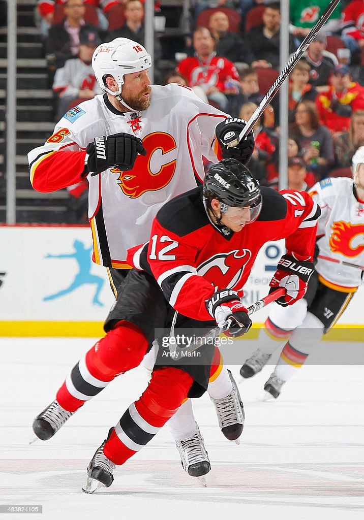 Brian McGrattan of the Calgary Flames and Damien Brunner of the New Jersey Devils battle for position during the game at the Prudential Center on...