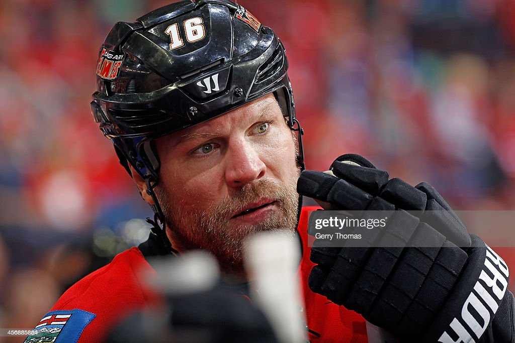 Brian McGrattan of the Calgary Flames stands by the bench during a stoppage in play against the Vancouver Canucks in their NHL season opener at...
