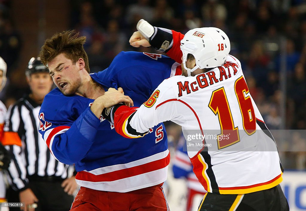 Brian McGrattan of the Calgary Flames throws a punch at Dylan McIlrath of the New York Rangers during their second period fight at Madison Square...