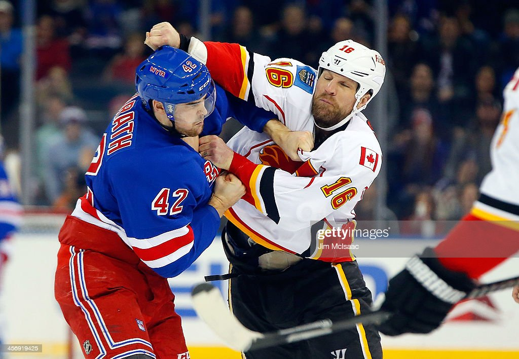 Brian McGrattan of the Calgary Flames trades punches with Dylan McIlrath of the New York Rangers during their second period fight at Madison Square...