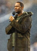 Brian McKnight sings the national anthem in the rain before NFL Network Thursday Night Football Game between the San Francisco 49ers and Seattle...