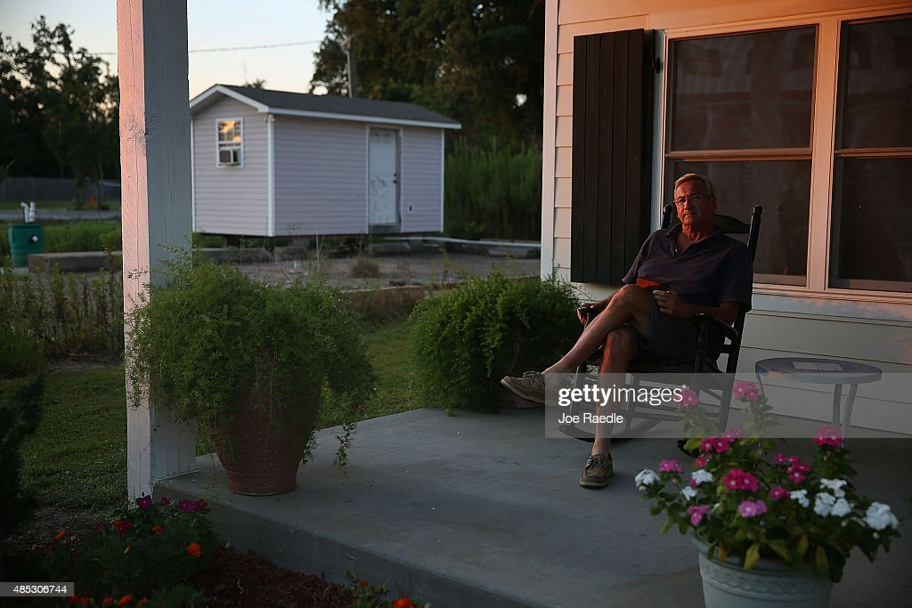 Brian Mollere sits with a box holding the remains of his dog Rocky on the porch of the home he rebuilt on the slab of his former home after Hurricane...