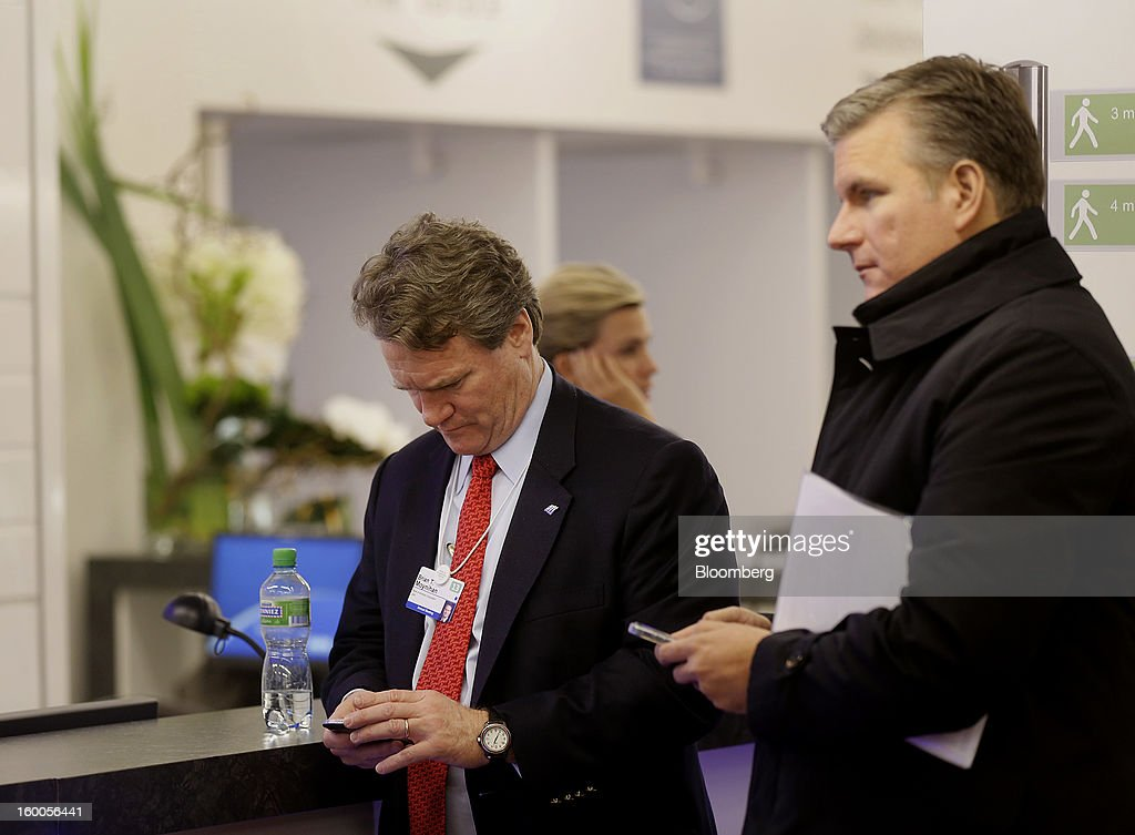 Brian Moynihan, president and chief executive officer of Bank of America Corp., left, checks his mobile phone inside the Congress Center on day three of the World Economic Forum (WEF) in Davos, Switzerland, on Friday, Jan. 25, 2013. World leaders, influential executives, bankers and policy makers attend the 43rd annual meeting of the World Economic Forum in Davos, the five day event runs from Jan. 23-27. Photographer: Simon Dawson/Bloomberg via Getty Images
