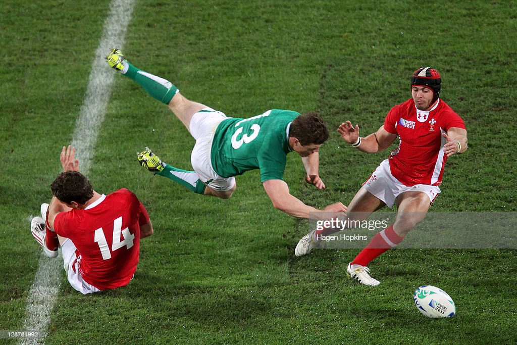 Brian O'Driscoll of Ireland flies through the air as he is tackled by <a gi-track='captionPersonalityLinkClicked' href=/galleries/search?phrase=George+North&family=editorial&specificpeople=7320853 ng-click='$event.stopPropagation()'>George North</a> (L) and <a gi-track='captionPersonalityLinkClicked' href=/galleries/search?phrase=Leigh+Halfpenny&family=editorial&specificpeople=4232760 ng-click='$event.stopPropagation()'>Leigh Halfpenny</a> (R) of Wales during quarter final one of the 2011 IRB Rugby World Cup between Ireland v Wales at Wellington Regional Stadium on October 8, 2011 in Wellington, New Zealand.