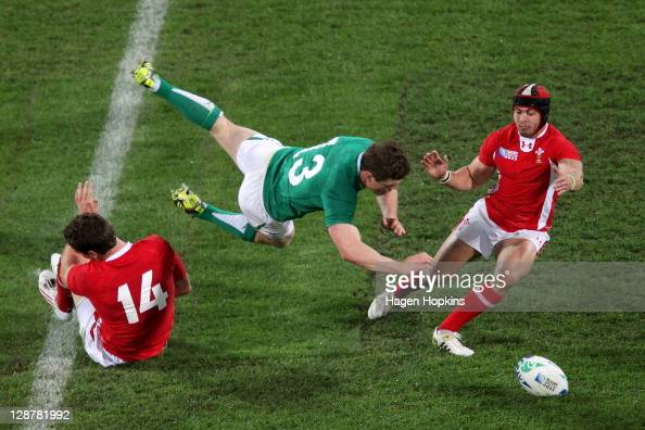 Brian O'Driscoll of Ireland flies through the air as he is tackled by George North and Leigh Halfpenny of Wales during quarter final one of the 2011...