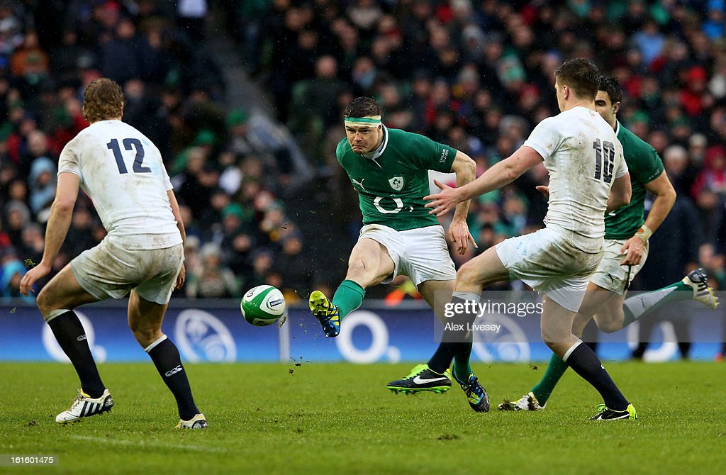 Brian O'Driscoll of Ireland kicks downfield past Billy Twelvetrees and Owen Farrell of England during the RBS Six Nations match between Ireland and England at Aviva Stadium on February 10, 2013 in Dublin, Ireland.