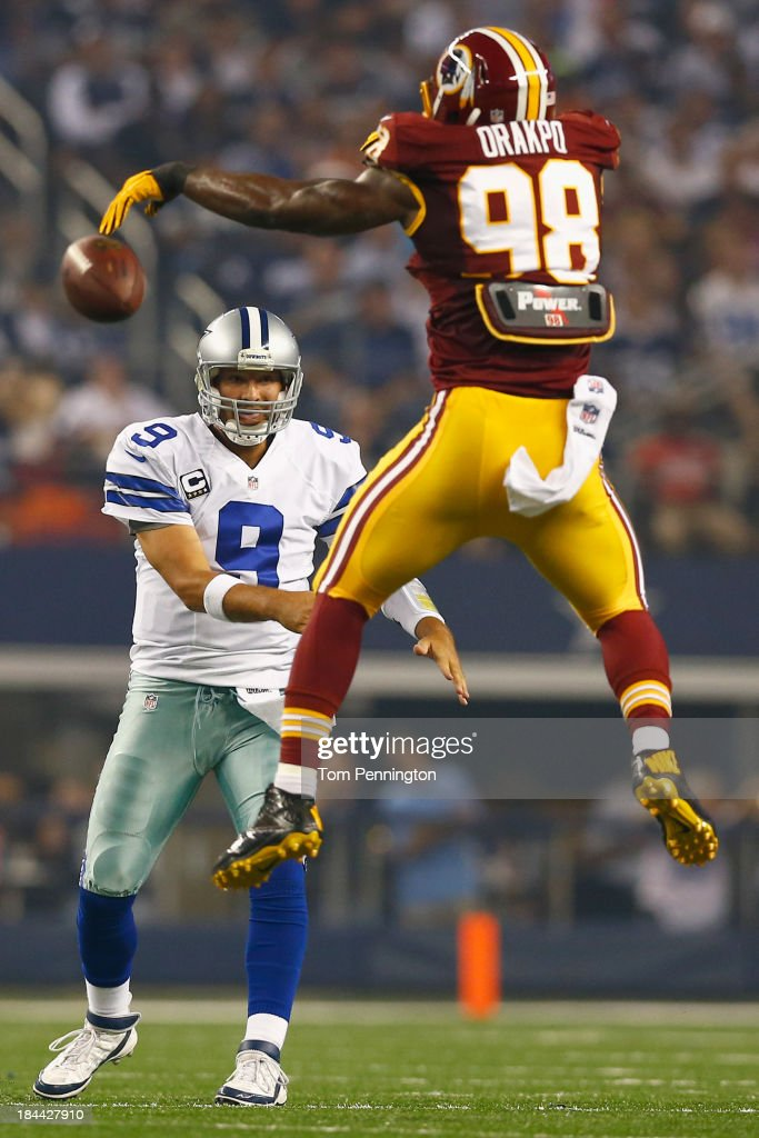 Brian Orakpo #98 of the Washington Redskins tips a pass thrown by Tony Romo #9 of the Dallas Cowboys in the second quarter on October 13, 2013 in Arlington, Texas.