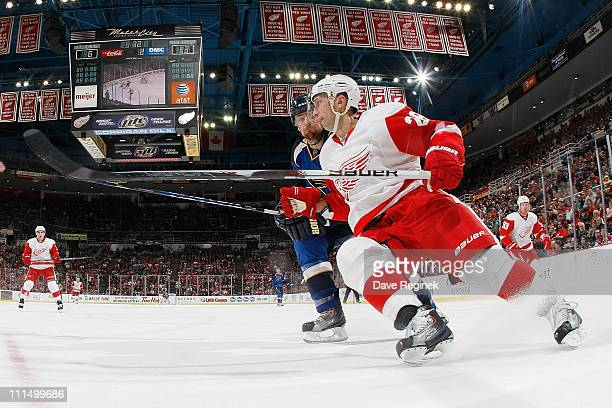 Brian Rafalski of the Detroit Red Wings braces for a body check from Chris Porter of the St Louis Blues during an NHL game at Joe Louis Arena on...