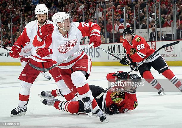 Brian Rafalski of the Detroit Red Wings charges toward the puck while Ben Smith of the Chicago Blackhawks falls next to Todd Bertuzzi of the Red...
