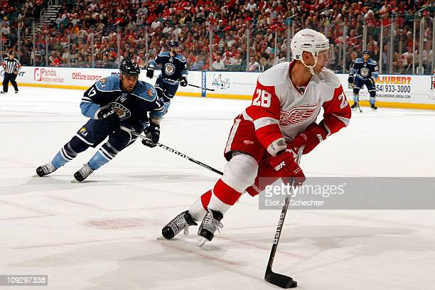 Brian Rafalski of the Detroit Red Wings skates with the puck against Kenndal McArdle of the Florida Panthers at the BankAtlantic Center on February...