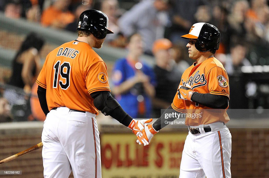 Brian Roberts #1 of the Baltimore Orioles celebrates with Chris Davis #19 after hitting a home run in the third inning against the Boston Red Sox at Oriole Park at Camden Yards on September 28, 2013 in Baltimore, Maryland.