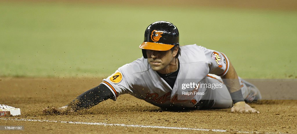 Brian Roberts #1 of the Baltimore Orioles dives back to first base on a pick off attempt by the Arizona Diamondbacks during the fifth inning of a MLB game at Chase Field on August 13, 2013 in Phoenix, Arizona.