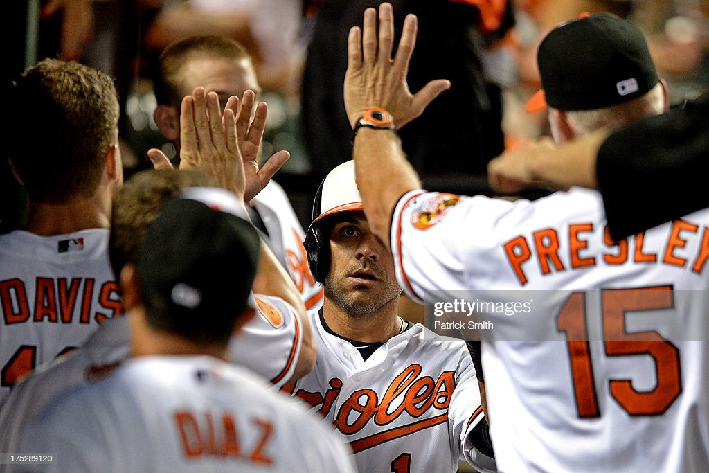 Brian Roberts #1 of the Baltimore Orioles is greeted in the dugout after scoring off of a Manny Machado #13 Baltimore Orioles hit in the fifth inning against the Houston Astros at Oriole Park at Camden Yards on August 1, 2013 in Baltimore, Maryland. The Baltimore Orioles won, 6-3.