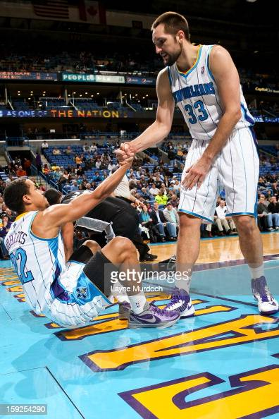 Brian Roberts of the New Orleans Hornets is helped up by teammate Ryan Anderson while playing against the San Antonio Spurs on January 7 2013 at the...