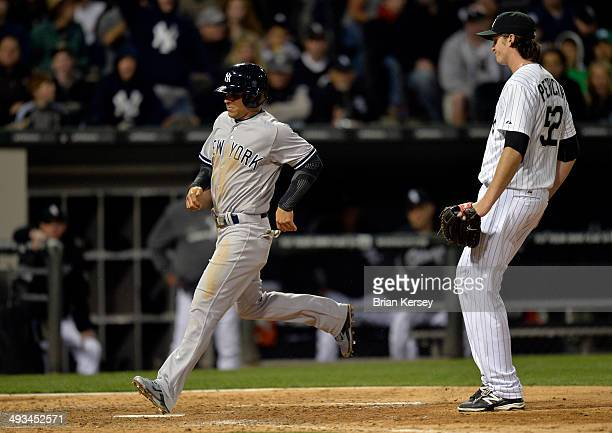 Brian Roberts of the New York Yankees scores on a wild pitch thrown by relief pitcher CC Sabathia of the New York Yankees during the seventh inning...
