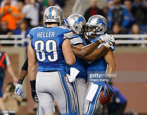 Brian Robiskie of the Detroit Lions celebrates a fourth quarter touchdown with Will Heller and Dominic Raiola at Ford Field on December 30 2012 in...