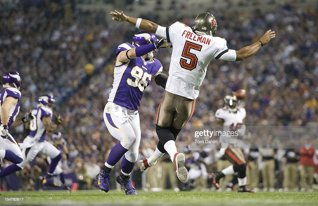 Brian Robison #96 of the Minnesota Vikings defends Josh Freeman #5 of the Tampa Bay Buccaneers during an NFL game against the Tampa Bay Buccaneers at Mall of America Field at the Hubert H. Humphrey Metrodome on October 25, 2012 in Minneapolis, Minnesota.