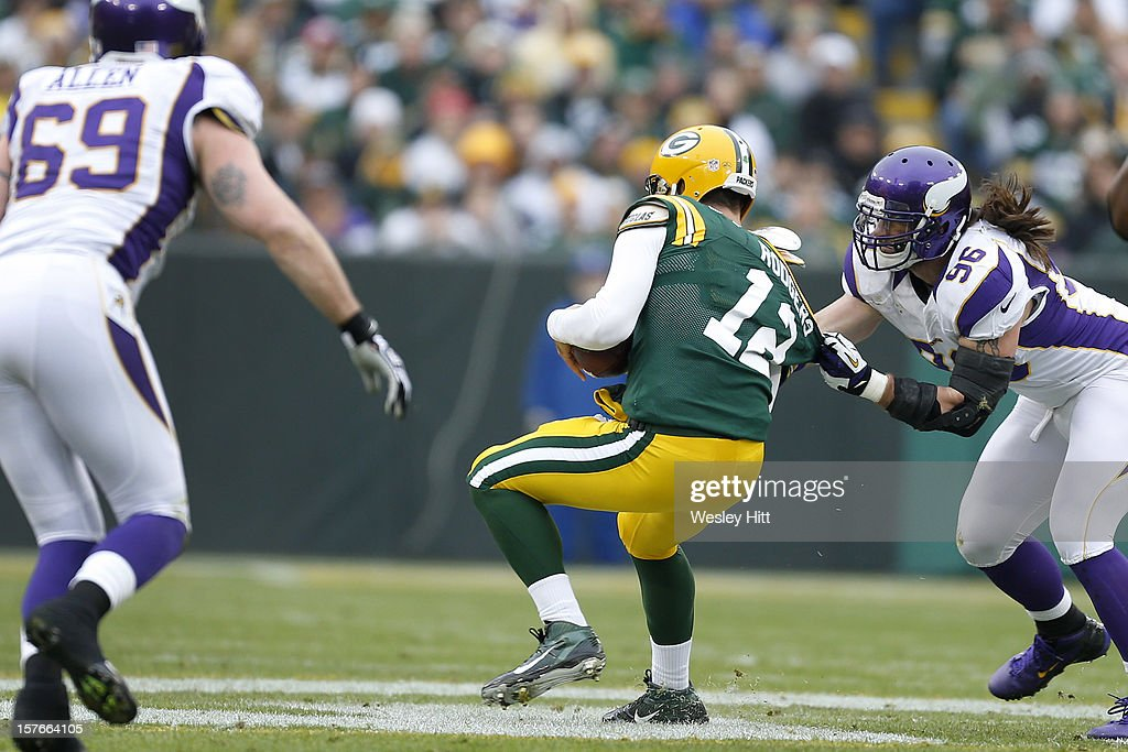 Brian Robison #96 of the Minnesota Vikings grabs Aaron Rodgers #12 of the Green Bay Packers at Lambeau Field on December 2, 2012 in Green Bay, Wisconsin. The Packers defeated the Vikings 23-14.