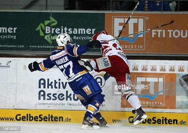 Brian Roloff of Augsburg Panther is hit hard by Ulrich Maurer during the DEL match between EHC Muenchen and Augsburger Panther on February 3 2012 in...