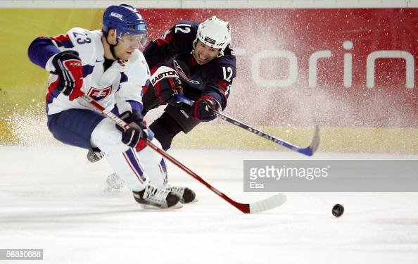 Brian Rolston of the United States battles Lubos Bartecko of Slovakia for control of the puck during the men's ice hockey Preliminary Round Group B...