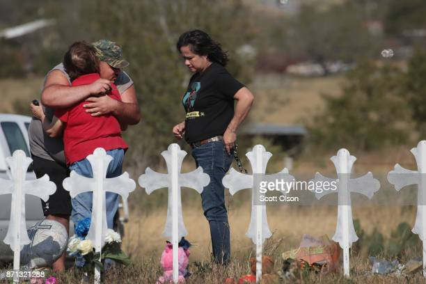 Brian Russell hugs Maria Durand while her daughter Lupita Alcoces watches during a visit to a memorial where 26 crosses stand in a field on the edge...