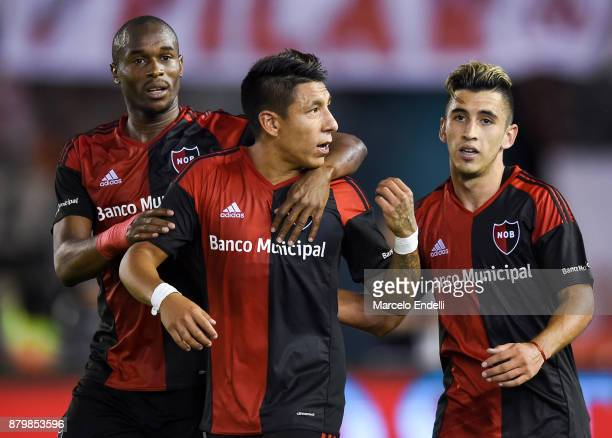 Brian Sarmiento of Newell's Old Boys celebrates with teammates Luis Leal and Joaquin Torres after scoring the second goal of his team during a match...
