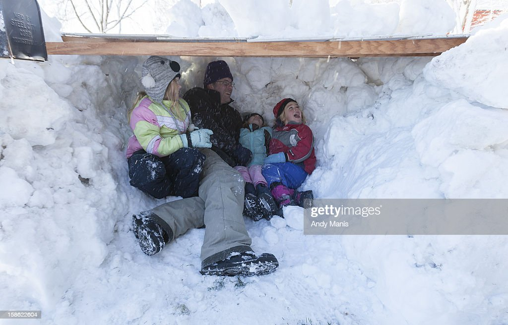 Brian Schmitt and his daughters Elise, left, 10, Julia, 6, and cousin Willa Treichel, right, 6, check out their newly made snow fort December 21, 2012 in Madison, Wisconsin. A day after a record snow storm hit Wisconsin, schools were closed Thursday and Friday.