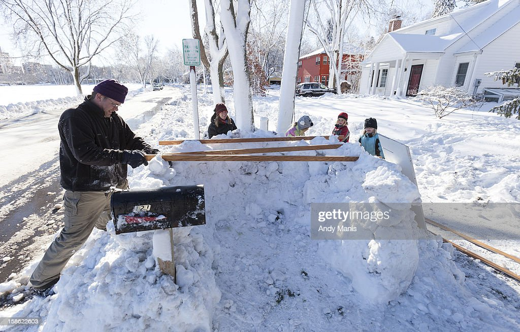 Brian Schmitt helps buid a snow fort along with family December 21, 2012 in Madison, Wisconsin. A day after a record snow storm hit Wisconsin, schools were closed Thursday and Friday.