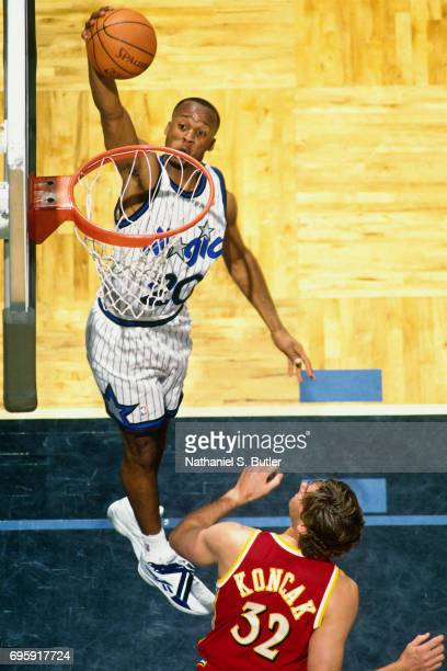 Brian Shaw of the Orlando Magic dunks against Jon Koncak of the Atlanta Hawks during a game played on March 5 1995 at Orlando Arena in Orlando...