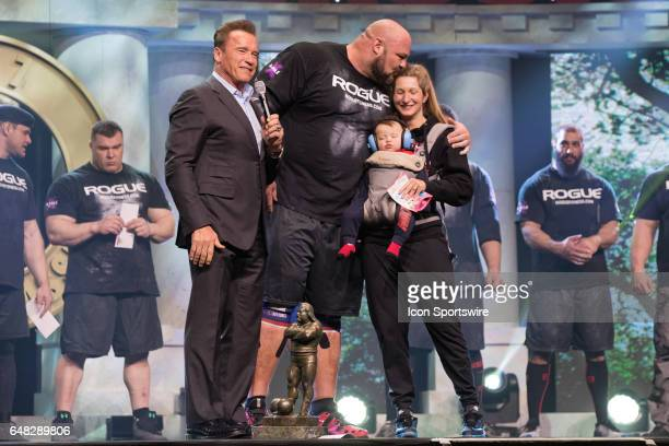 Brian Shaw on stage with his wife and infant son after being interviewed by Arnold Schwarzenegger after winning the 2017 Arnold Strongman Classic as...