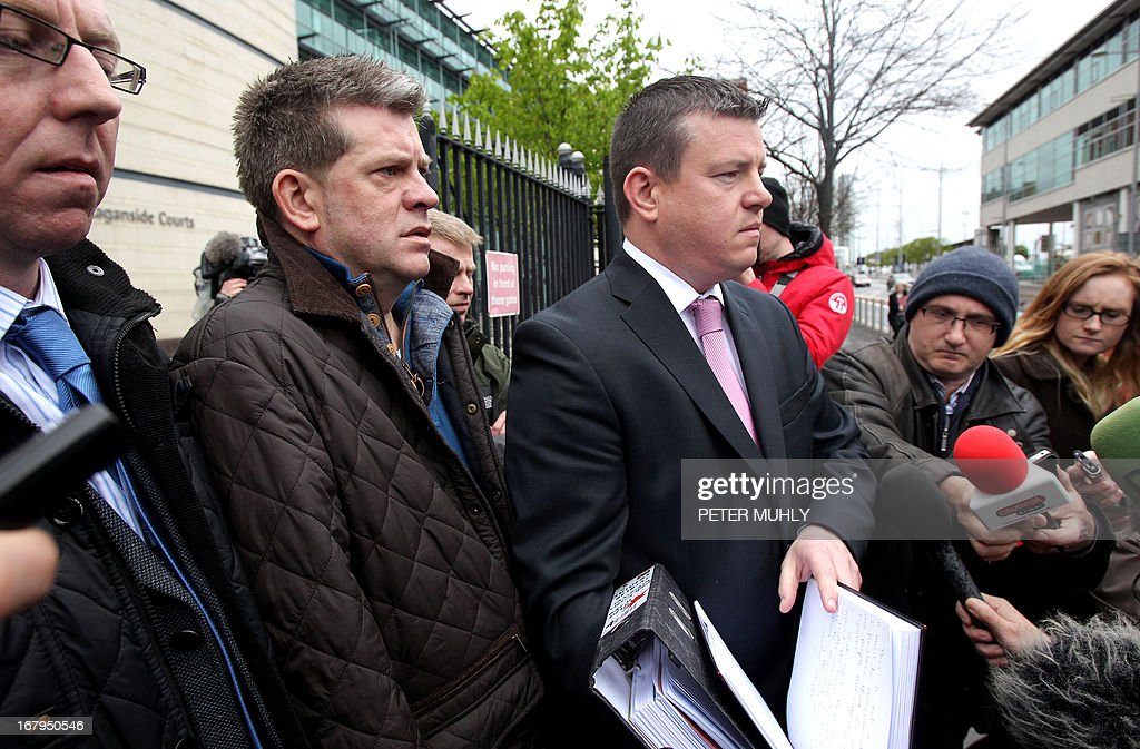 Brian Shivers (2nd L) looks on as his lawyer Naill Murphy (R) reads out a brief statement to the media outside Belfast High Court in Belfast, Northern Ireland on May 3, 2013 after the former was acquitted in a retrial of the murder of two British soldiers. Last year, Shivers, 47, was convicted of the murders of Mark Quinsey, 23, and Patrick Azimkar, 21, and ordered to serve at least 25 years, but that judgement was quashed earlier this year by Northern Ireland's Court of Appeal. AFP PHOTO/ PETER MUHLY