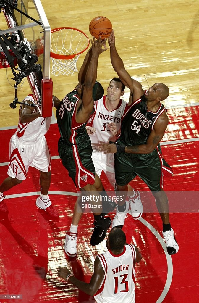 Brian Skinner of the Milwaukee Bucks shoots over Scott Padgett and Luther Head of the Houston Rockets and Mike Harris of the Milwaukee Bucks during a...