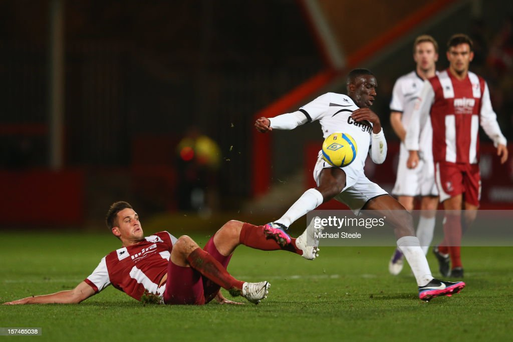 Brian Smikle (R) of Hereford United hurdles a challenge from Darren Carter (L) of Cheltenham Town during the FA Cup with Budweiser Second Round match between Cheltenham Town and Hereford United at the Abbey Business Stadium on December 3, 2012 in Cheltenham, England.