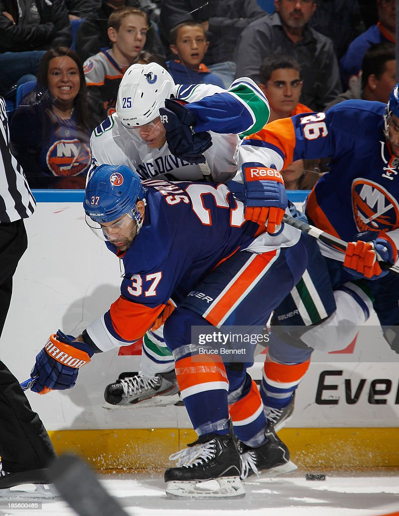 <a gi-track='captionPersonalityLinkClicked' href=/galleries/search?phrase=Brian+Strait&family=editorial&specificpeople=570466 ng-click='$event.stopPropagation()'>Brian Strait</a> #37 of the New York Islanders gets under <a gi-track='captionPersonalityLinkClicked' href=/galleries/search?phrase=Mike+Santorelli&family=editorial&specificpeople=4517042 ng-click='$event.stopPropagation()'>Mike Santorelli</a> #25 of the Vancouver Canucks at the Nassau Veterans Memorial Coliseum on October 22, 2013 in Uniondale, New York. The Canucks defeated the Islanders 5-4 in overtime.