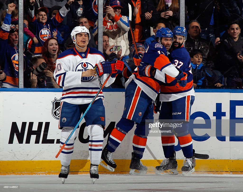 Brian Strait #37 of the New York Islanders grabs Colin McDonald #13 following McDonalds goal at 13:20 of the first period against the Edmonton Oilers at the Nassau Veterans Memorial Coliseum on February 10, 2015 in Uniondale, New York.