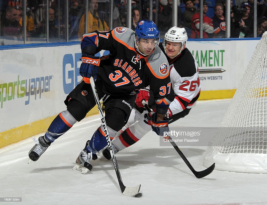 Brian Strait #37 of the New York Islanders holds off Patrik Elias #26 of the New Jersey Devils as he skates with the puck during the game on February 3, 2013 at Nassau Veterans Memorial Coliseum in Uniondale, New York.