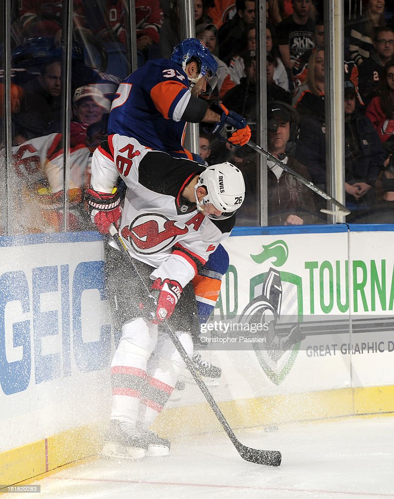Brian Strait #37 of the New York Islanders is checked by Patrik Elias #26 of the New Jersey Devils during the game on February 16, 2013 at Nassau Veterans Memorial Coliseum in Uniondale, New York.