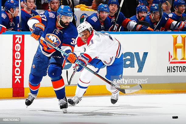 Brian Strait of the New York Islanders is pursued by Devante SmithPelly of the Montreal Canadiens at Nassau Veterans Memorial Coliseum on March 14...