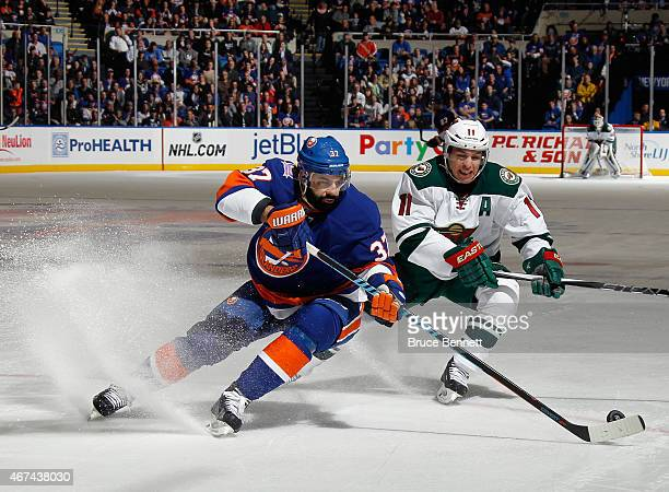 Brian Strait of the New York Islanders moves the puck as he is checked by Zach Parise of the Minnesota Wild during the first period at the Nassau...