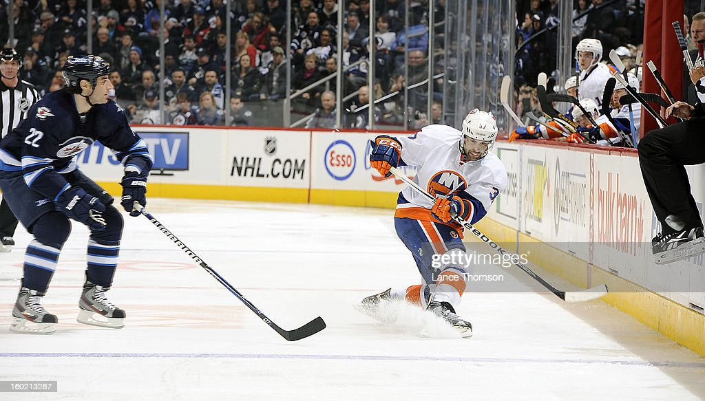 Brian Strait #37 of the New York Islanders shoots the puck down the ice as <a gi-track='captionPersonalityLinkClicked' href=/galleries/search?phrase=Chris+Thorburn&family=editorial&specificpeople=2222066 ng-click='$event.stopPropagation()'>Chris Thorburn</a> #22 of the Winnipeg Jets looks on during third period action at the MTS Centre on January 27, 2013 in Winnipeg, Manitoba, Canada.