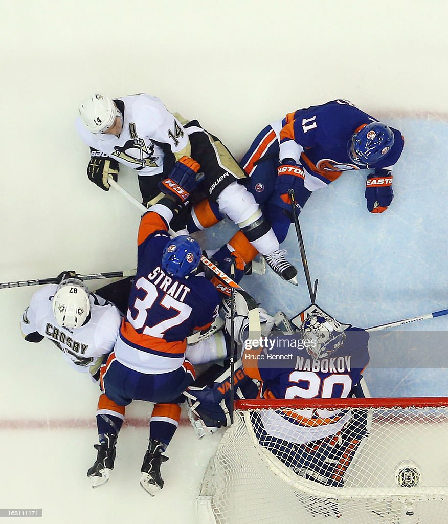 <a gi-track='captionPersonalityLinkClicked' href=/galleries/search?phrase=Brian+Strait&family=editorial&specificpeople=570466 ng-click='$event.stopPropagation()'>Brian Strait</a> #37 of the New York Islanders takes a holding penalty in overtime against <a gi-track='captionPersonalityLinkClicked' href=/galleries/search?phrase=Sidney+Crosby&family=editorial&specificpeople=212781 ng-click='$event.stopPropagation()'>Sidney Crosby</a> #87 of the Pittsburgh Penguins in Game Three of the Eastern Conference Quarterfinals during the 2013 NHL Stanley Cup Playoffs at the Nassau Veterans Memorial Coliseum on May 5, 2013 in Uniondale, New York. The Penguins defeated the Islanders 5-4 in overtime.