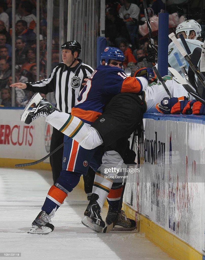 Brian Sutherby #20 of the Dallas Stars is hit by Mike Mottau #10 of the New York Islanders at the Nassau Coliseum on October 9, 2010 in Uniondale, New York. The Stars defeated the Islanders 5-4 in the shootout.