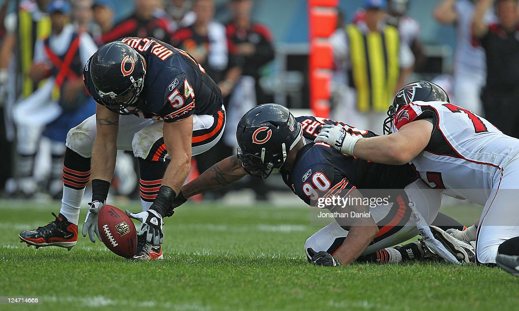 Brian Urlacher of the Chicago Bears pics up a fumble that's out of the reach of teammate Julius Peppers as Sam Baker of the Atlanta Falcons holds...