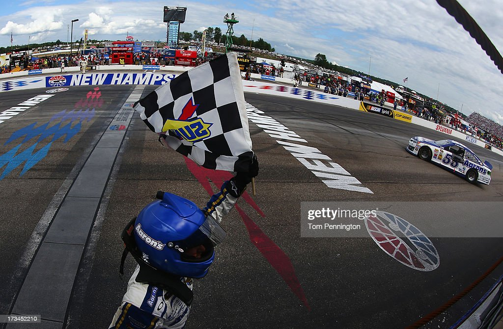 Brian Vickers, driver of the #55 Aaron's Dream Machine Toyota, celebrates with the checkered flag after winning the NASCAR Sprint Cup Series Camping World RV Sales 301 at New Hampshire Motor Speedway on July 14, 2013 in Loudon, New Hampshire.
